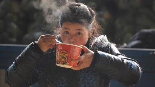 대도시로 유입되는 농민공들의 숫자가 줄면서 중국의 컵라면 소비도 줄고 있다. 사진은 베이징의 여성 농민공이 컵라면을 먹는 모습. BBC중문망 캡처