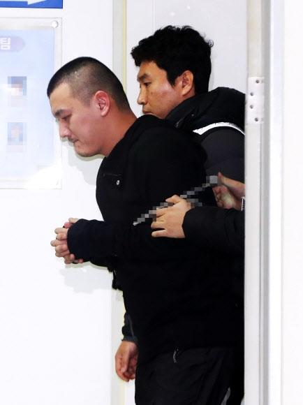 얼굴 공개된 '용인 일가족 살해범' 김성관 재가한 어머니의 일가족을 살해하고 뉴질랜드로 도피했다 국내로 송환돼 구속된 김성관(35)씨가 14일 오후 경기도 용인시 용인동부경찰서에서 오전 조사를 마치고 유치장으로 이동하고 있다. 연합뉴스