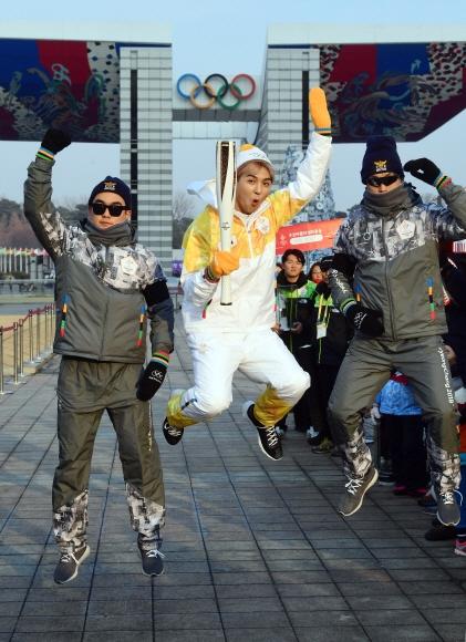 14일 서울 올림픽공원에서 가수 송민호씨가 성화를 들고 점프를 하고 있다.  정연호 기자 tpgod@seoul.co.kr