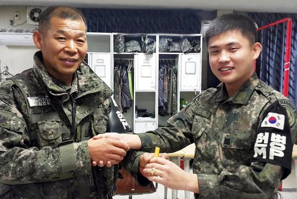 육군 28사단 김만수(왼쪽) 원사가 전역을 앞둔 모범용사에게 도장과 반지를 선물한 뒤 악수하고 있다. 육군 제공