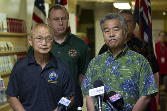 13일(현지시간) 데이비드 이게(앞줄 오른쪽) 하와이 주지사와 번 미야기(왼쪽) HEMA 국장이 다이아몬드헤드의 비상관리센터에서 긴급 기자회견을 열고 혼란을 야기한 원인을 설명하고 사과하고 있다.  하와이 AP 연합뉴스
