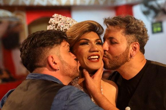 지난달 14일 콜롬비아에서 열린 '제7회 미스 세뇨라 게이 콜롬비아 선발대회(Gay Miss Senora Colombia)'에서 왕관을 차지한 훌리엣 멘도사가 대회 주최측 남성들에게 축하 키스를 받고 있다. AFP 연합뉴스