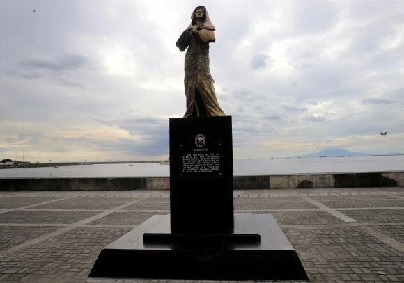 """필리핀 마닐라 로하스 대로에 제막된 위안부 피해자 동상. 필리핀 전통 의상을 입은 여성이 눈가리개를 하고 있는 모습의 이 동상 밑에는 """"1942~1945년 일본 점령기 동안 성폭력에 희생된 필리핀 여성을 기억한다""""는 글이 적혀 있다.  로이터 연합뉴스"""