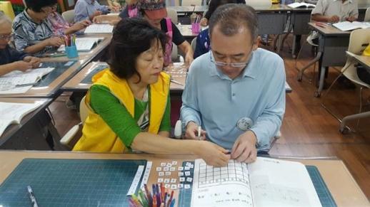 한 경증 치매 노인이 서울 성동구 치매지원센터의 기억키움학교에서 달력 만들기 활동을 하고 있다. 성동구 제공