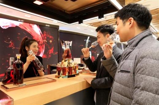 18일 인천공항 제2여객터미널 롯데면세점 플래그십 매장을 찾은 고객들이 주류 제품을 시음해 보고 있다. 롯데면세점 제공