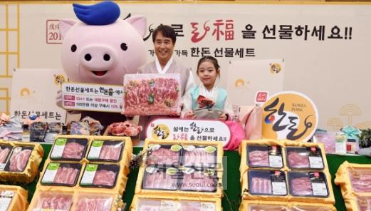 """""""설 선물은 한돈""""  24일 서울 세종문화회관에서 열린 '설 한돈 선물세트 사진행사'에서 하태식 한돈자조금관리위원장과 어린이 모델이 포즈를 취하고 있다. 한돈자조금은 온라인 공식 쇼핑몰인 '한돈몰'(mall.han-don.com)에서 시중보다 저렴하게 설 선물세트를 판매한다고 밝혔다. 정연호 기자 tpgod@seoul.co.kr"""