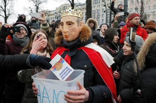 조롱거리 된 '거리의 푸틴'  28일(현지시간) 러시아 모스크바 시내 중심가에서 한 시민이 왕관을 쓰는 블라디미르 푸틴 대통령의 마스크를 착용한 채 다른 시위 참가자로부터 러시아 연방 헌법 내용이 적힌 책자를 받고 있다. 이날 러시아 전국 곳곳에선 오는 3월 대통령 선거에서 4번째 연임을 노리는 푸틴 대통령의 유일한 '대항마'였던 알렉세이 나발니의 출마가 좌절된 데 대한 '대선 보이콧' 시위가 열렸다. 모스크바 EPA 연합뉴스