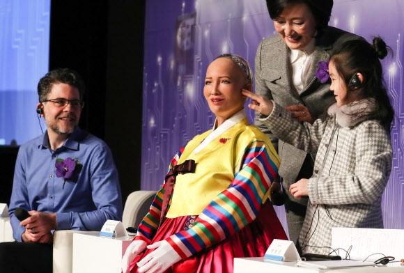 """""""헬로 소피아""""  30일 서울 중구 더프라자호텔에서 열린 '4차 산업혁명, 로봇 소피아에게 묻다' 콘퍼런스에서 한 어린이가 인공지능(AI) 로봇 소피아(왼쪽 두 번째)의 피부를 만져 보고 있다. 행사에는 소피아를 만든 핸슨 로보틱스의 최고경영자인 데이비드 핸슨(왼쪽)과 박영선(오른쪽 두 번째) 더불어민주당 의원이 참석했다. 연합뉴스"""