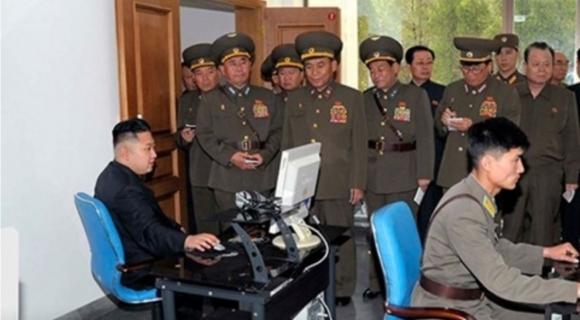 북한 김정은 노동당 위원장이 군인들이 지켜보는 가운데 컴퓨터를 작동하고 있다.