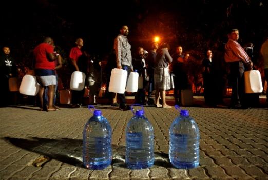 지난달 25일(현지시간) 남아프리카공화국 케이프타운 뉴랜즈 용천수 지역에서 시민들이 생활용수를 확보하려고 물통을 들고 줄 서 있다. 기후변화와 시 당국의 무능으로 케이프타운은 물 공급을 완전 중단하는 '데이 제로'(Day Zero)까지 치닫고 있다. 케이프타운 로이터 연합뉴스