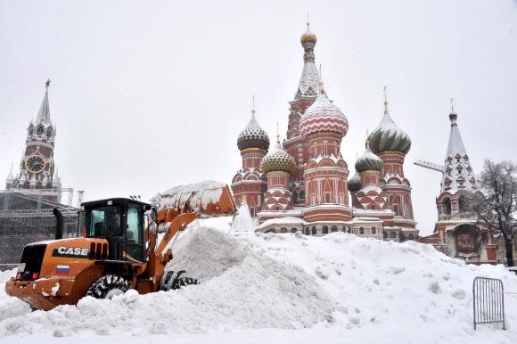 사상 최고 43㎝ 폭설에 마비된 모스크바 4일(현지시간) 기록적인 폭설이 내린 러시아 모스크바 거리에서 불도저가 삽으로 쌓인 눈을 치우고 있다. 기상 관측 이래 최고치인 적설량 43㎝를 기록한 이번 폭설로 1명이 사망하고 5명이 다쳤다. 또 나무 수천 그루가 쓰러지면서 주변 마을 수백 곳이 집단 정전 사태를 겪었고, 지하철과 항공기 운항도 차질을 빚는 등 도시가 마비됐다. 모스크바 AFP 연합뉴스