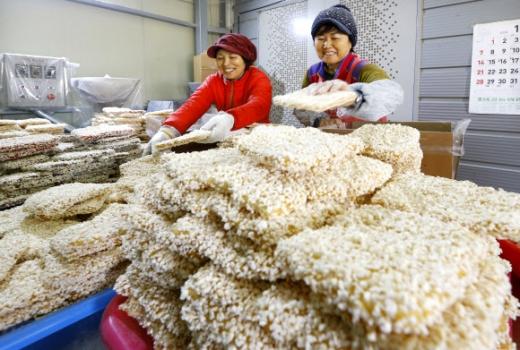 올림픽 보며 설맞이  설 명절을 엿새 앞둔 9일 전북 정읍의 한 한과 공장에서 직원들이 밝은 얼굴로 제품을 포장하고 있다. 정읍 연합뉴스