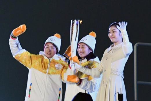 제23회 평창동계올림픽이 9일 막을 올렸다. 사진은 27년 만에 결성된 남북 단일팀 여자 아이스하키 선수인 박종아(가운데)와 정수현(왼쪽)이 성화대 바로 앞에서 성화봉을 든 채 관중에게 손을 흔들고 있다.  평창 박지환 기자 popocar@seoul.co.kr
