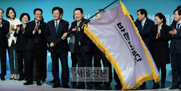 경기 고양시 일산 킨텍스에서 13일 열린 바른미래당 출범대회에서 유승민·박주선 공동대표가 함께 당기를 흔들고 있다. 국민의당 안철수 대표는 합당과 동시에 2선으로 물러났다. 이종원 선임기자 jongwon@seoul.co.kr