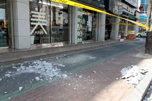 지난 11일 경북 포항에서 규모 4.6 지진이 난 이후 포항시 북구 장성동 한 건물에서 부서진 외벽 조각이 인도에 떨어져 있다.  연합뉴스