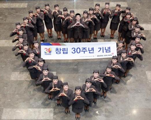 아시아나항공 신입 승무원들이 14일 서울 강서구 본사에서 창립 30돌을 자축하며 하트를 만들어 보이고 있다.  아시아나항공 제공