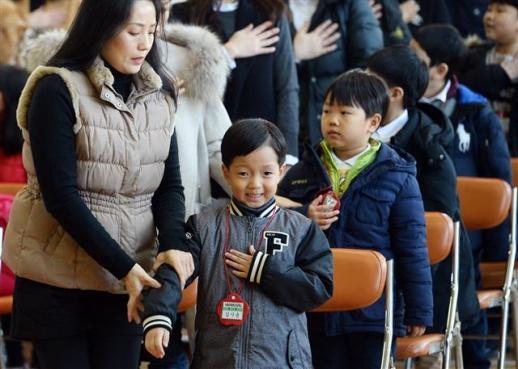 지난해 3월 서울 용산구 이태원초등학교에서 열린 입학식에서 한 학부모가 국기에 대한 경례를 하며 왼손을 가슴에 올린 자녀의 자세를 고쳐 주고 있는 모습.  서울신문 DB