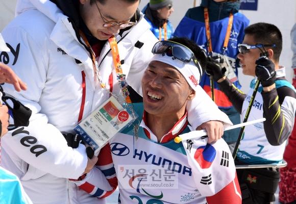 11일 강원 평창 바이애슬론센터에서 열린 평창동계패럴림픽 크로스컨트리스키 남자 좌식 15㎞에서 3위로 결승선을 끊은 신의현(오른쪽)이 배동현 선수단장에게 축하를 받으며 함박웃음을 짓고 있다. 평창 박윤슬 기자 seul@seoul.co.kr