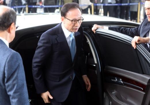 자택에서 출발한 지 8분 만에 검찰청사에 도착한 이 전 대통령이 차량에서 내려 취재진의 포토라인으로 향하고 있다.  사진공동취재단