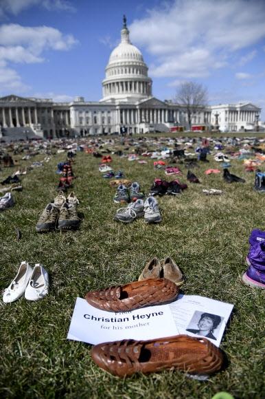 총격 희생 학생 7000명 대신한 신발시위  13일(현지시간) 미국 워싱턴DC 국회의사당 앞 잔디밭에 사회운동가들이 펼쳐 놓은 7000켤레의 신발이 놓여 있다. 이들은 2012년 코네티컷주 뉴타운의 샌디훅 초등학교에서 벌어진 총기 난사 사건 이후 총격으로 희생된 7000명의 학생들을 추모하는 뜻으로 주인 잃은 신발들을 펼쳐 놓고 총기규제 입법을 촉구했다.  워싱턴 AFP 연합뉴스