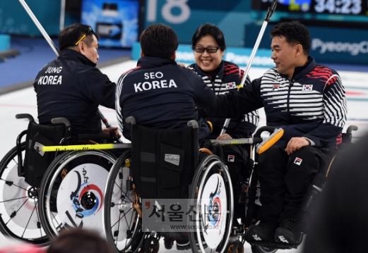휠체어 컬링 대표팀이 14일 저녁 강원 강릉컬링센터에서 열린 평창동계패럴림픽 예선 9차전에서 스웨덴을 격파한 뒤 모여 하이파이브를 하고 있다.  강릉 박윤슬 기자 Seul@seoul.co.kr