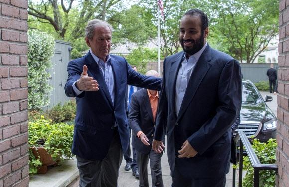 양복 입은 빈살만  아랍 왕실 옷차림이 아닌 정장을 입은 무함마드 빈살만(오른쪽) 사우디아라비아 제1 왕위계승자(왕세자) 겸 국방장관이 지난 7일(현지시간) 미국 텍사스주 휴스턴의 조지 W 부시(왼쪽) 전 미국 대통령의 안내를 받아 부시 가문 자택에 들어서고 있다. 빈살만 왕세자는 이날 만남을 비롯해 첨단 정보기술(IT) 분야의 주요 인사와 회동할 때 쿠피야(전통 두건)와 사웁(옷)을 벗어던지고 정장을 입어 화제를 모았다.  휴스턴 AFP 연합뉴스
