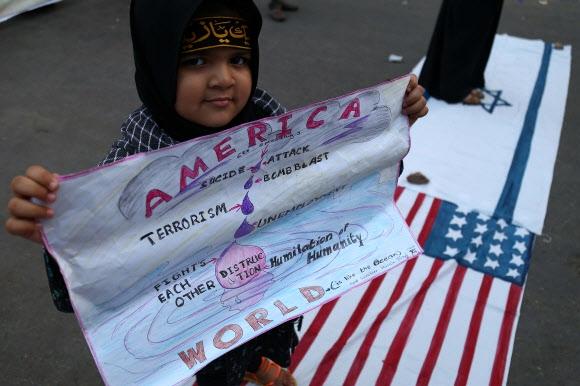지구촌 곳곳 반전 시위 15일(현지시간) 전 세계에서 미국과 영국·프랑스 연합군의 시리아 공습을 반대하는 시위가 이어진 가운데 파키스탄 카라치에서 시아파 무슬림 학생 조직 소속의 소녀가 '미국이 전 세계를 파괴한다'는 내용의 팻말을 들고 시리아 공습을 규탄하고 있다. 카라치 EPA 연합뉴스
