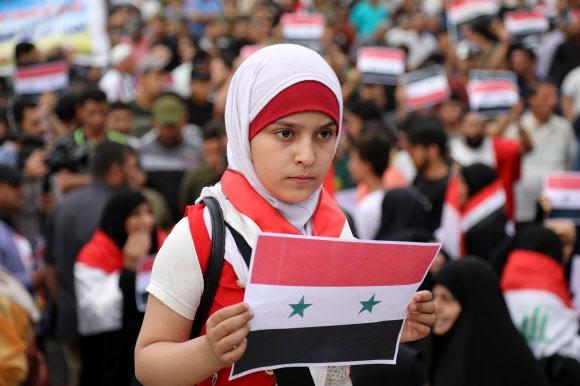 지구촌 곳곳 반전 시위 15일(현지시간) 전 세계에서 미국과 영국·프랑스 연합군의 시리아 공습을 반대하는 시위가 이어진 가운데 이라크 바그다드에서 한 소녀가 시리아 국기를 들고 연합국의 시리아 공습에 항의하고 있다. 바그다드 신화 연합뉴스