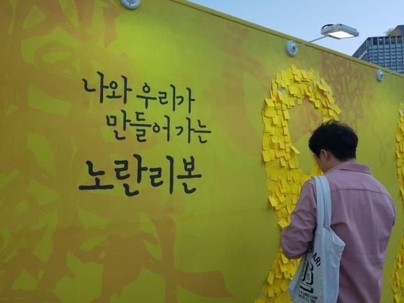 세월호 4주년을 맞은 16일 서울 종로구 광화문 광장에서 열린 4.16 기억 전시장 한편에 마련된 추모 공간에서 한 시민이 추모의 마음을 담은 포스트잇을 붙이고 있다.