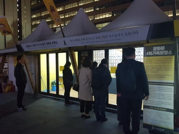 세월호 참사 4주년을 맞은 16일 밤 10시 30분쯤 낮에 미처 분향소를 찾지 못한 시민들이 잠긴 분향소 바깥에서 희생자들을 위해 묵념하고 있다.