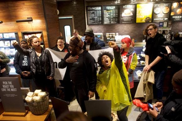 """스타벅스 CEO """"흑인 차별 논란 사과"""" 커피전문점 스타벅스 점원의 인종차별적 행위에 분노한 시민들이 16일(현지시간) 미국 펜실베이니아주 필라델피아 스타벅스 매장에서 항의 시위를 하고 있다. 지난 12일 이 매장의 점원이 음료를 주문하지 않고 자리에 앉아 있던 흑인 남성 2명을 경찰에 신고해 체포된 사건이 발생했다. 당시 상황을 촬영한 영상과 증언 등이 소셜네트워크서비스(SNS) 등을 통해 삽시간에 퍼지면서 논란이 일고 불매 운동으로까지 번졌다. 케빈 존슨 스타벅스 CEO는 피해 남성을 찾아 사과하기로 했다. 필라델피아 로이터 연합뉴스"""