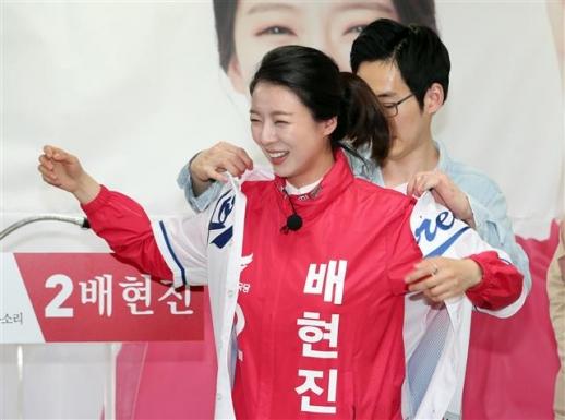 배현진 자유한국당 송파을 예비후보가 13일 오후 서울 송파구에 위치한 선거사무소 개소식에서 청년들에게 야구 유니폼을 선물받고 있다.  뉴스1