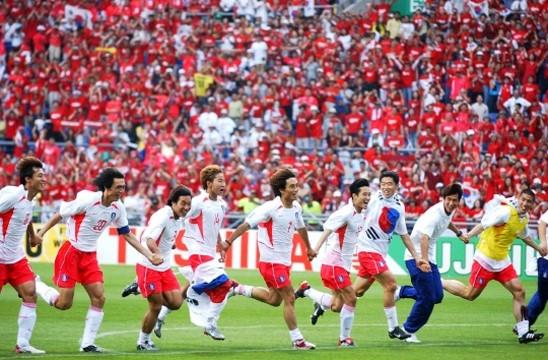 2002년 한일웓드컵 당시 8강전에서 승부차기 끝에 스페인을 따돌리고 4강신화를 일궈낸 태극전사들이 태극기를 휘감고 그라운드를 내달리고 있다.[서울신문 DB]