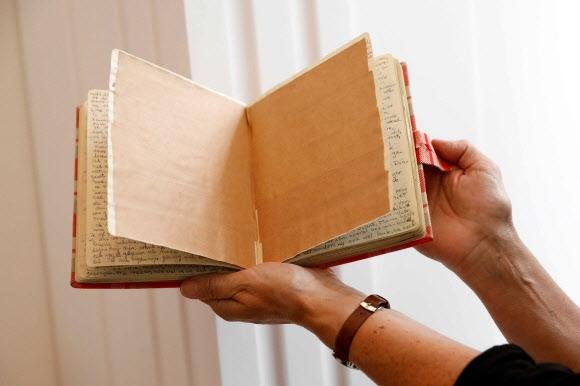 안네 프랑크 박물관 관계자가 15일(현지시간) 네덜란드 암스테르담에 있는 박물관에서 안네 프랑크가 쓴 일기장에 갈색 종이를 붙인 부분을 펼쳐 보이고 있다. 암스테르담 EPA 연합뉴스