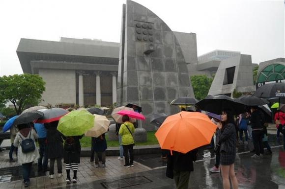 지난 12일 비가 오는 가운데 참가자들이 건립 40주년을 맞은 세종문화회관 옆 세종로공원 안 전기통신 발상지 기념탑을 둘러보고 있다. 조선시대 당시에는 사헌부와 병조가 자리한 육조거리였다.