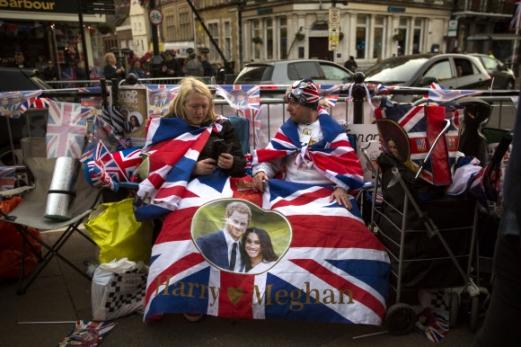노숙하며 결혼식 축하  19일(현지시간) 결혼하는 영국 해리 왕자와 미국 배우 메건 마클의 열혈 지지자들이 16일 결혼식장인 런던 인근 원저성 밖에서 신랑, 신부의 사진을 새긴 영국 국기를 펼쳐 놓고 앉아 있다.  런던 AP 연합뉴스