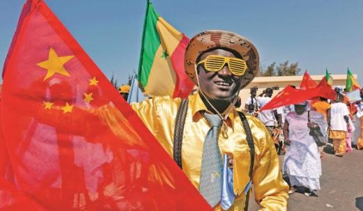 지난 2009년 세네갈 다카르 국제공항에서 한 시민이 후진타오 중국 국가주석이 도착하자 중국 국기인 오성홍기를 흔들며 환영하고 있다.  서울신문 DB