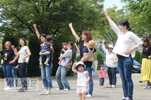 """지난달 17일 일본 가이즈카시 중앙공민관 건물 앞에서 육아네트워크 영유아부회 엄마들이 아이와 함께 춤 연습을 하고 있다. 임신 9개월째인 이누이 사오리(29·오른쪽 첫 번째)는 """"엄마들과 함께 고민하고 육아 조언을 들을 수 있어 좋다""""고 미소를 지었다."""