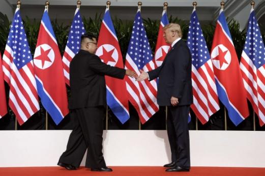 싱가포르 센토사섬 카펠라 호텔에서 만난 김정은 북한 국무위원장이 도널드 트럼프 미국 대통령에게 다가가면서 악수를 하기 위해 손을 내밀고 있다. 2018. 6. 12. AP 연합뉴스