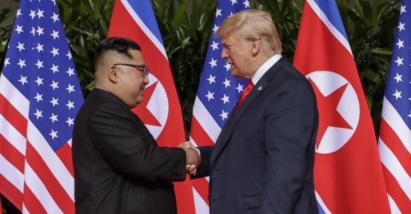 도널드 트럼프(오른쪽) 미국 대통령과 김정은 북한 국무위원장이 정상회담을 위해 12일 싱가포르 센토사섬 카펠라 호텔에서 만나 악수하고 있다. AP 연합뉴스