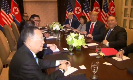 김정은 북한 국문위원장과 도널드 트럼프 미국 대통령을 포함한 북한과 미국 당국자들이 싱가포르 센토사섬 카펠라호텔에서 확대정상회담을 하면서 환하게 웃고 있다. 2018.6.12 현지 방송 캡쳐·AP 연합뉴스