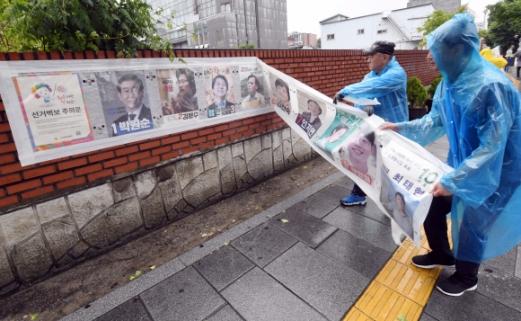 14일 서울 종로구 청운동 효자주차장 앞에서 주민센터 직원들이 제7회 전국동시지방선거벽보를 철거하고 있다. 2018. 6. 14 정연호 기자 tpgod@seoul.co.kr