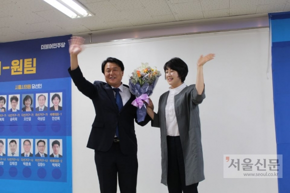 임병택 시흥시장 당선인이 지방선거에서 압승을 거두고 축하꽃다발을 부인 김보영씨와 함께 들고 환하게 웃고 있다. 임병택 당선인측 제공