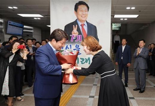 자유한국당 권영진(왼쪽) 대구시장 당선자가 14일 대구시청에서 환영 나온 직원으로부터 축하 꽃다발을 받고 있다.  대구 뉴스1