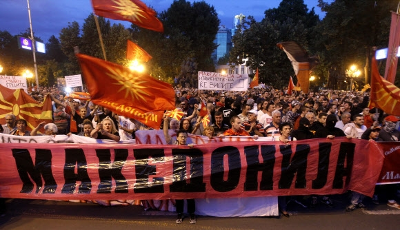 """마케도니아 국민 """"내 나라 이름 못 바꾼다""""  27년째 '국명 전쟁'을 이어 온 그리스와 마케도니아 양국 총리가 지난 12일 마케도니아의 이름을 '북마케도니아 공화국'으로 고치는 데 극적으로 합의했지만 양국 국민들의 거센 반발에 직면했다. 사진은 13일(현지시간) 마케도니아 수도 스코페 국회의사당 앞에서 피켓을 든 채 시위하고 있는 시민들.  스코페 AP 연합뉴스"""