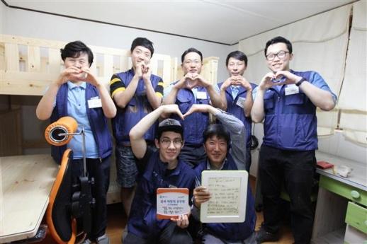 GS건설 직원들이 저소득층 가정 공부방 '꿈과 희망의 공부방'에서 손으로 하트를 그려 보이고 있다.  GS건설 제공