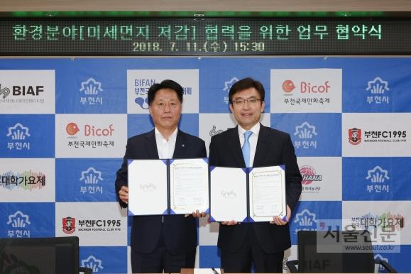 장덕천(왼쪽) 부천시장과 나희승 한국철도기술연구원장이 도로미세먼지 저감사업 협약서를 들어보이고 있다. 부천시 제공