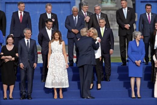 도널드 트럼프(앞줄 왼쪽 네 번째) 미국 대통령이 11일(현지시간) 벨기에 브뤼셀에서 열린 나토 정상회의 기념 촬영 도중 에마뉘엘 마크롱 프랑스 대통령의 부인 브리지트 트로뇌와 볼을 맞대는 프랑스식 인사 '비주'를 하고 있다. 앞줄 왼쪽 첫 번째는 트럼프 대통령의 부인 멜라니아. 브뤼셀 EPA 연합뉴스