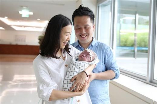 초미숙아로 태어난 사랑이의 어머니 이인선씨와 아버지 이충구씨가 사랑이를 품에 안고 활짝 웃고 있다.  서울아산병원 제공