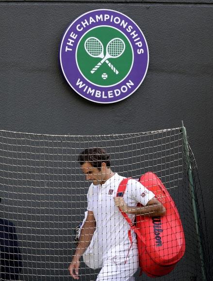 '테니스 황제' 로저 페더러가 12일 런던 올잉글랜드 테니스클럽에서 끝난 윔블던 테니스대회 남자단식 8강전에서 남아공의 케빈 앤더슨에게 2-3으로 역전패한 뒤 고개를 숙인 채 코트를 빠져나가고 있다.  런던 AP 연합뉴스